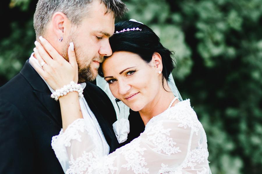 Braut hält das Gesicht vom Bräutigam, Hochzeitspaar steht verliebt zusammen, Hochzeitsfotografie