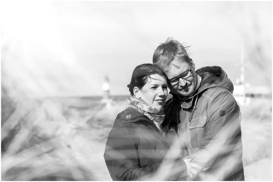 paar-steht-eng-zusammen-koepfe-lehnen-aneinander-im-hintergrund-leuchtturm-warnemuende-engagementshooting-ostsee-shooting-am-strand-paarshooting-paarfotografie-fotograf-warnemünde-fotograf-rostock