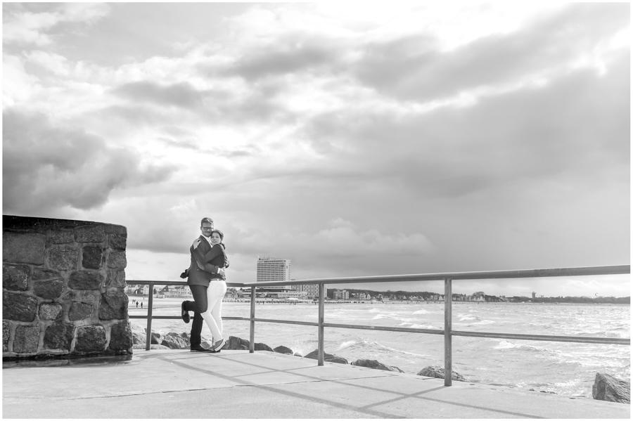 paerchen-umarmt-sich-auf-mole-von-warnemünde-im-hintergrund-ostseestrand-hotel-neptun-engagementshooting-ostsee-shooting-am-strand-paarshooting-paarfotografie-fotograf-warnemünde-fotograf-rostock