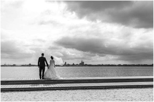 Brautpaar steht am Strandufer von Altefähr und schaut Richtung Stralsund - Hochzeitsfotografie in Altefähr - Hochzeitsfotograf_Ruegen_Stralsund