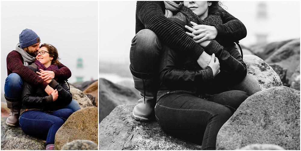 paar-eng-umarmt-frau-laechelt-sitzen-auf-steinen-an-der-mole-warnemuende-fotoshooting-am-strand-paerchenbilder-fotograf-warnemuende-fotograf-rostock