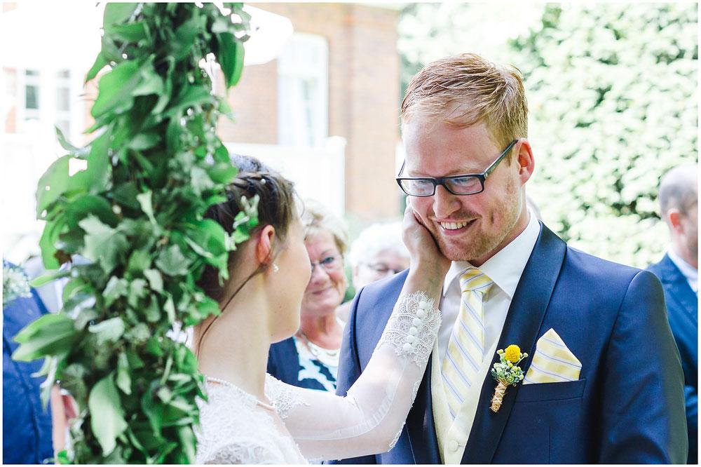 freie Trauung Braut_streichelt_liebevoll_Braeutigam_Hochzeitsfotograf_Ruegen_Rostock_Richterfotografie_Hochzeitsfotografie auf Rügen