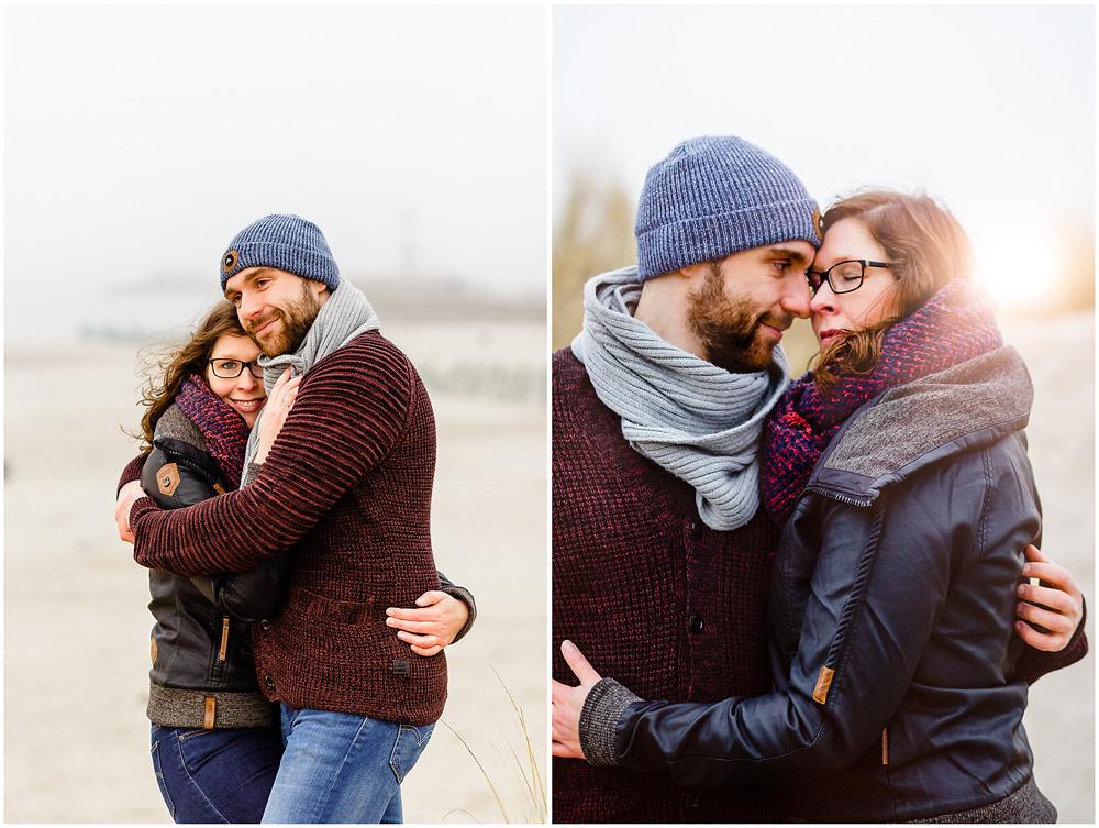 portraitfoto-liebespaar-umarmt-sich-eng-koepfe-aneinander-gelehnt-fotoshooting-am-strand-paerchenbilder-fotograf-warnemuende-fotograf-rostock