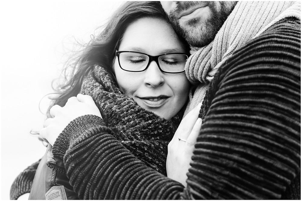 portraitfoto-liebespaar-eng-umarmt-frau-lehnt-mit-kopf-an-schulter-vom-mann-fotoshooting-am-strand-paerchenbilder-fotograf-warnemuende-fotograf-rostock