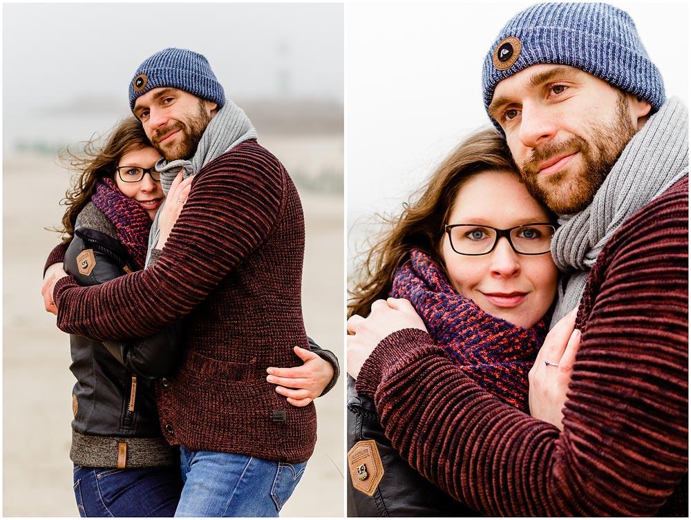 portraitfoto-liebespaar-eng-umarmt-beide-laecheln-fotoshooting-am-strand-paerchenbilder-fotograf-warnemuende-fotograf-rostock