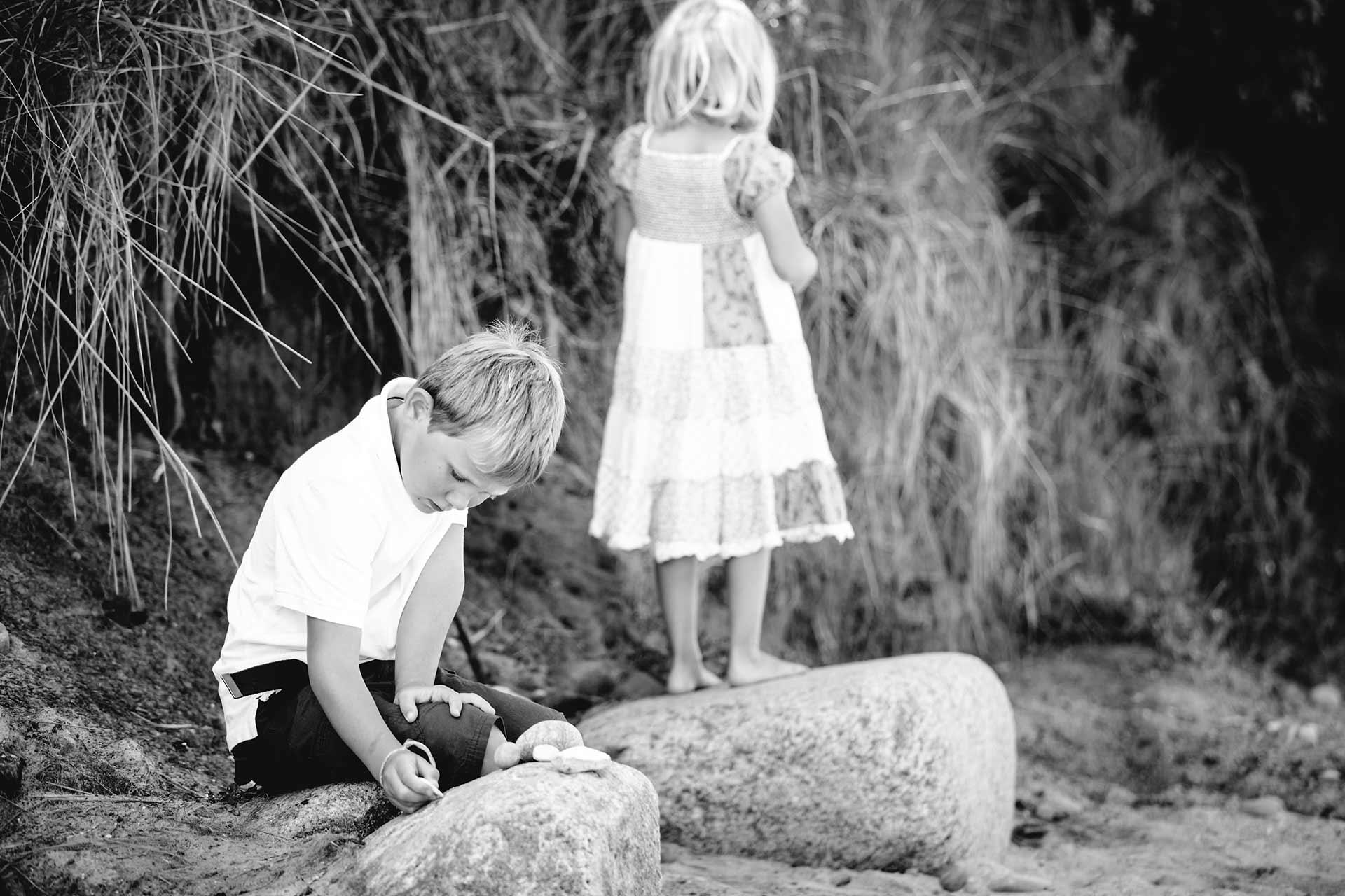 Junge-sitzt-vertraeumt-auf-grossem-Stein-am-Strand-Shooting-am-Strand-Familienfotografie-Fotograf-Rostock - Familienshooting