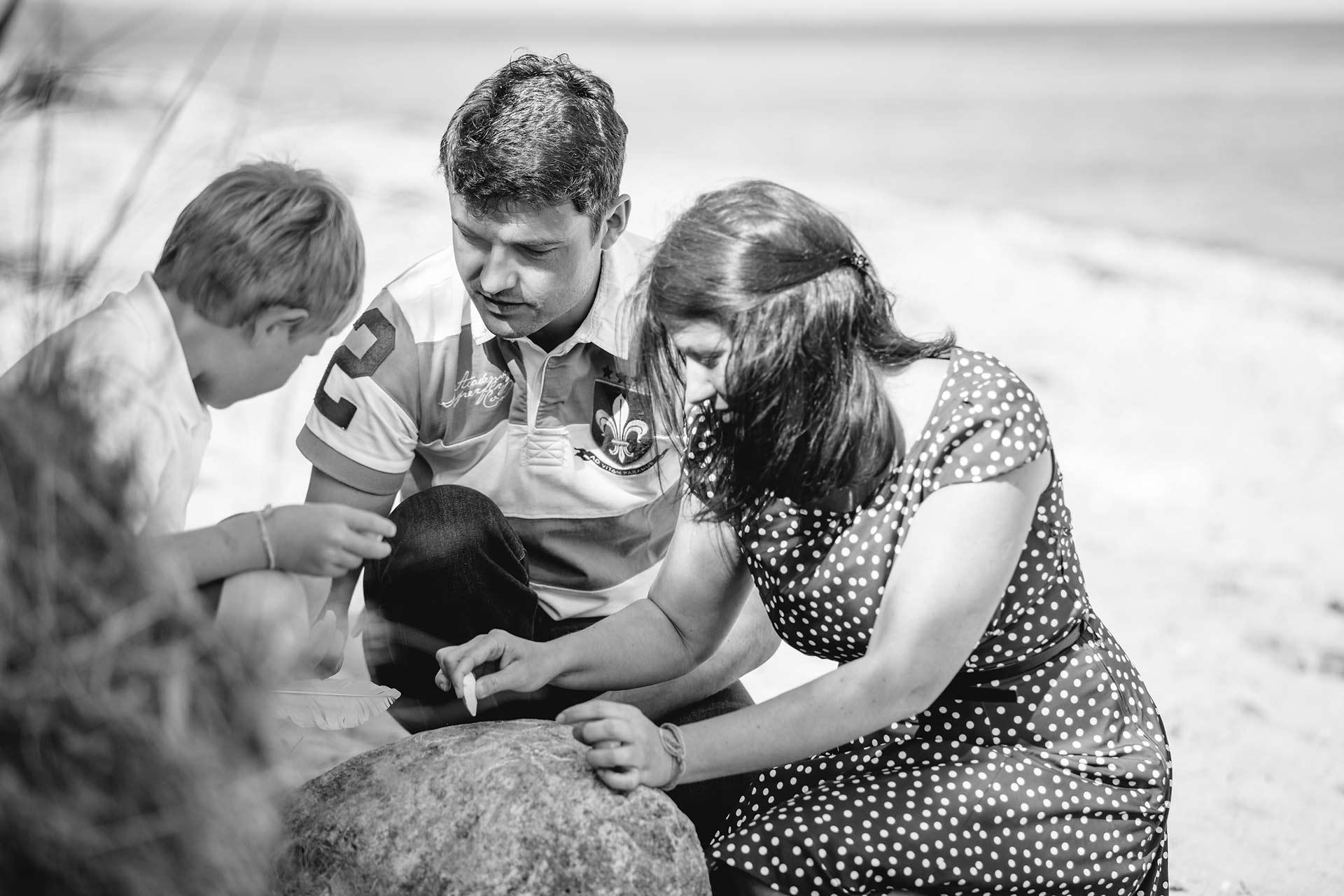 Mama-Papa-und-Sohn-spielen-am-Strand-Junge-sitzt-vertraeumt-auf-grossem-Stein-am-Strand-Shooting-am-Strand-Familienfotografie-Fotograf-Rostock - Familienshooting