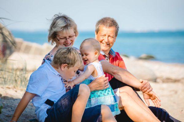 im-vordergrund-sitzen-Junge-und-Baby-dahinter-Oma-und-Opa-Shooting-am-Strand-Familienfotografie-Fotograf-Rostock - Familienshooting
