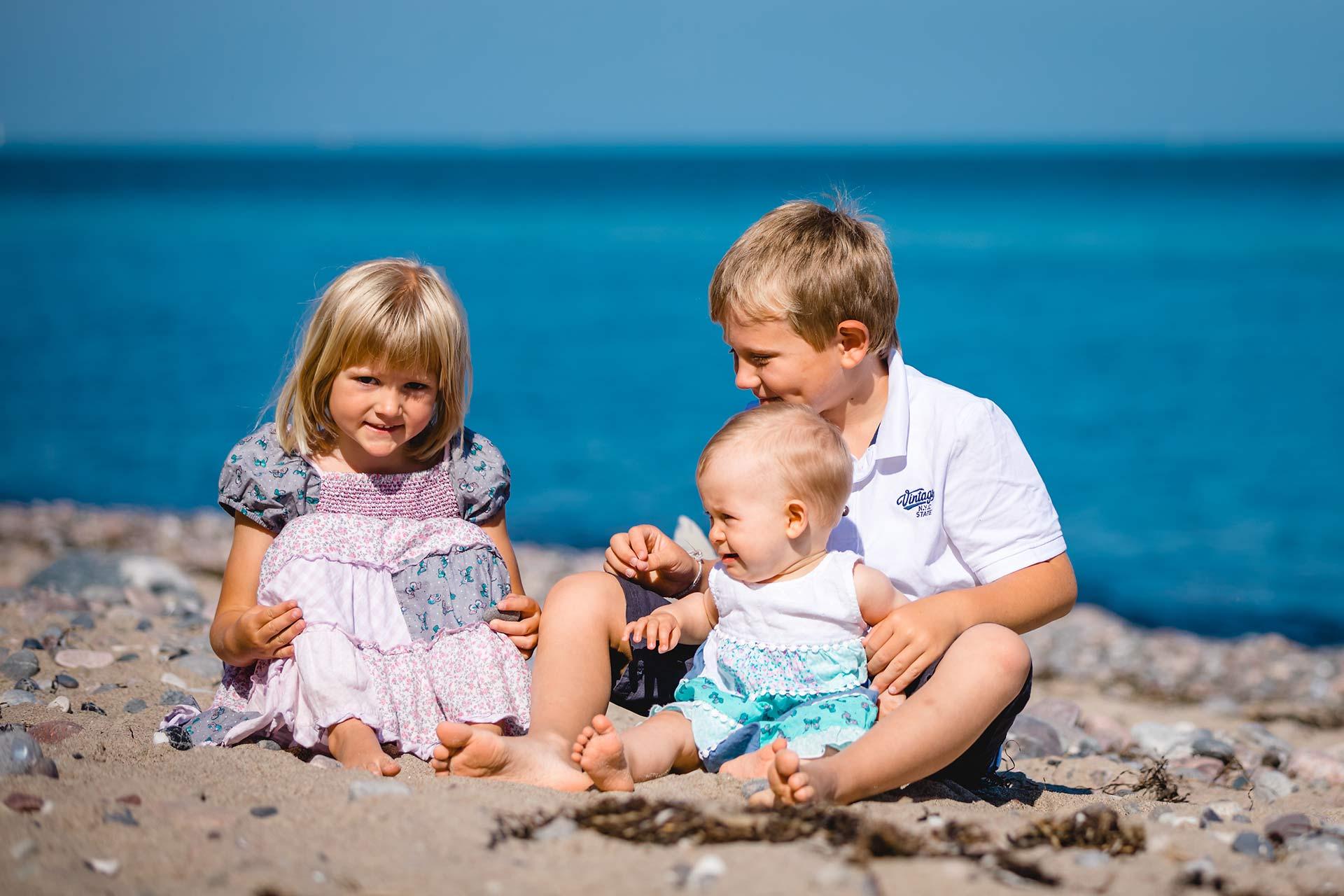 Maedchen-Junge-und-Baby-sitzen-im-Sand-Ostseestrand-Shooting-am-Strand-Familienfotografie-Fotograf-Rostock - Familienshooting
