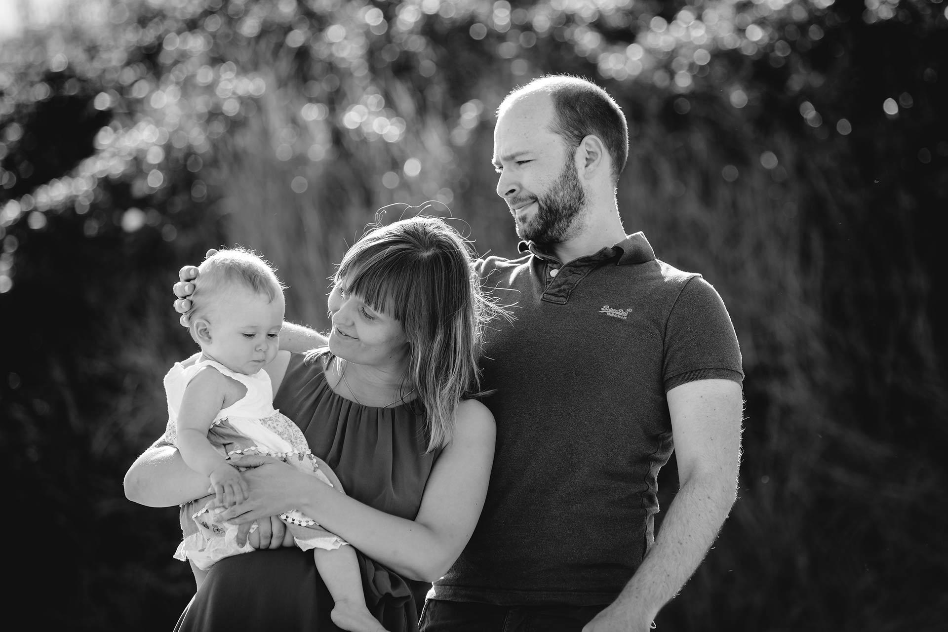 Mutter-haelt-ihr-Baby-auf-dem-Arm-Vater-streichelt-Baby-am-Kopf-Shooting-am-Strand-Familienfotografie-Fotograf-Rostock - Familienshooting
