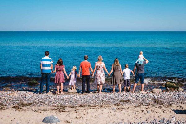 ganze-Familie-steht-Hand-in-Hand-direkt-am-Wasser-Ostsee-Shooting-am-Strand-Familienfotografie-Fotograf-Rostock - Familienshooting