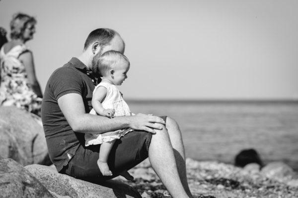 Papa-sitzt-auf-grossem-Stein-mit-seinem-Baby-aud-dem-schoss-Shooting-am-Strand-Familienfotografie-Fotograf-Rostock - Familienshooting