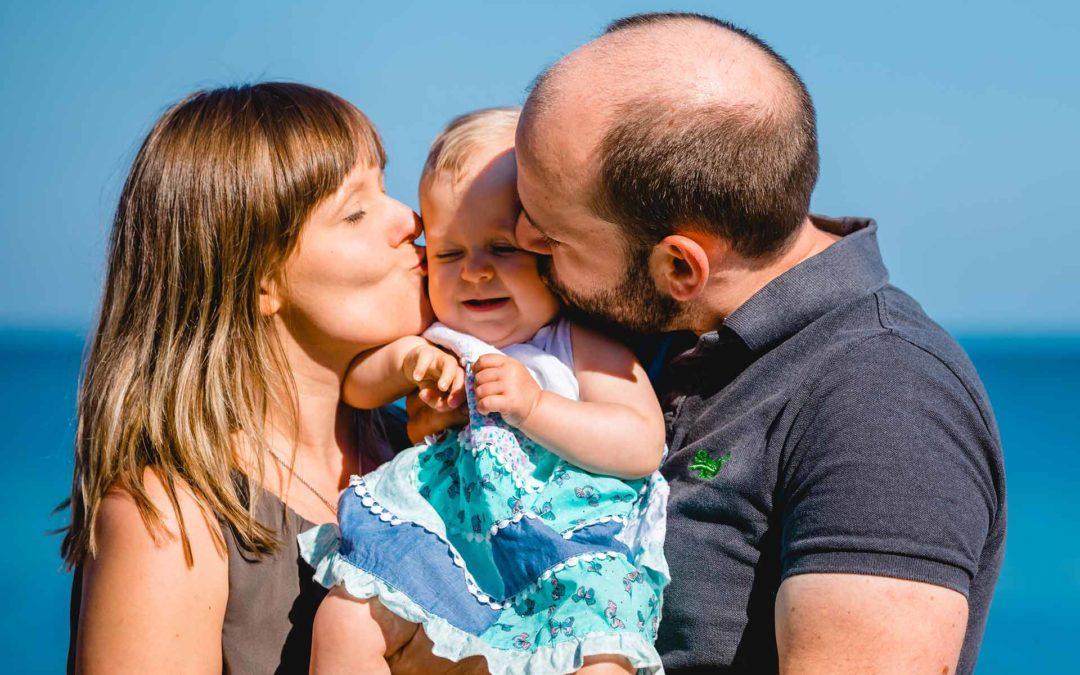 Familienshooting am Strand - Mama und Papa kuessen Baby gleichzeitig auf Wange - Shooting am Strand - Familienfotografie - Fotograf Rostock - Familienshooting