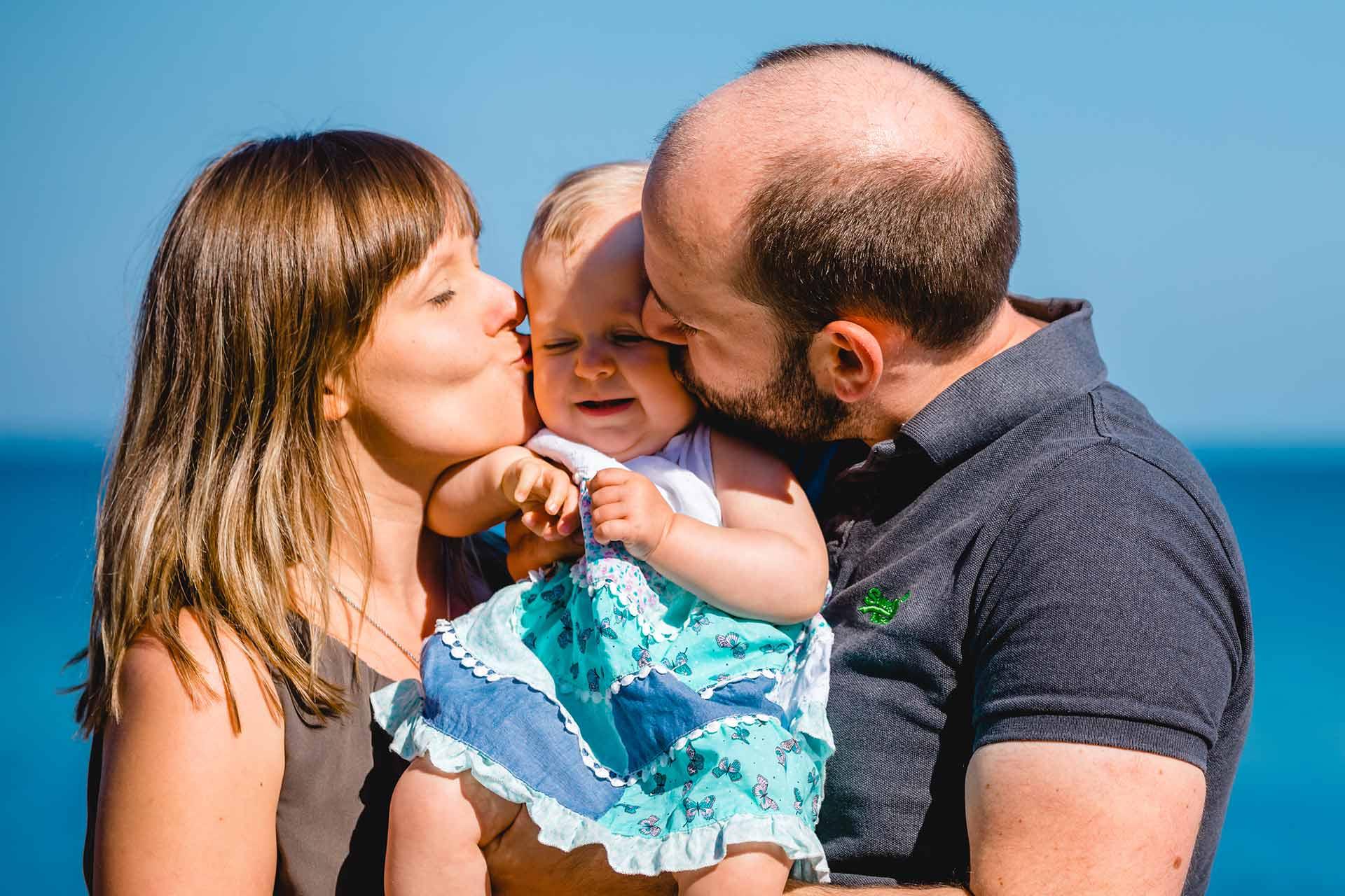 Mama-und-Papa-kuessen-Baby-gleichzeitig-auf-Wange-Shooting-am-Strand-Familienfotografie-Fotograf-Rostock - Familienshooting