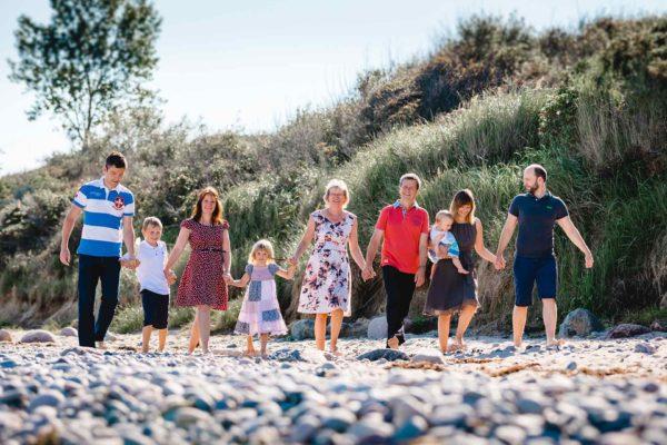 drei-Generationen-neun-Menschen-gehen-Hand-in-Hand-am-Strand-Shooting-am-Strand-Familienfotografie-Fotograf-Rostock-Familienshooting