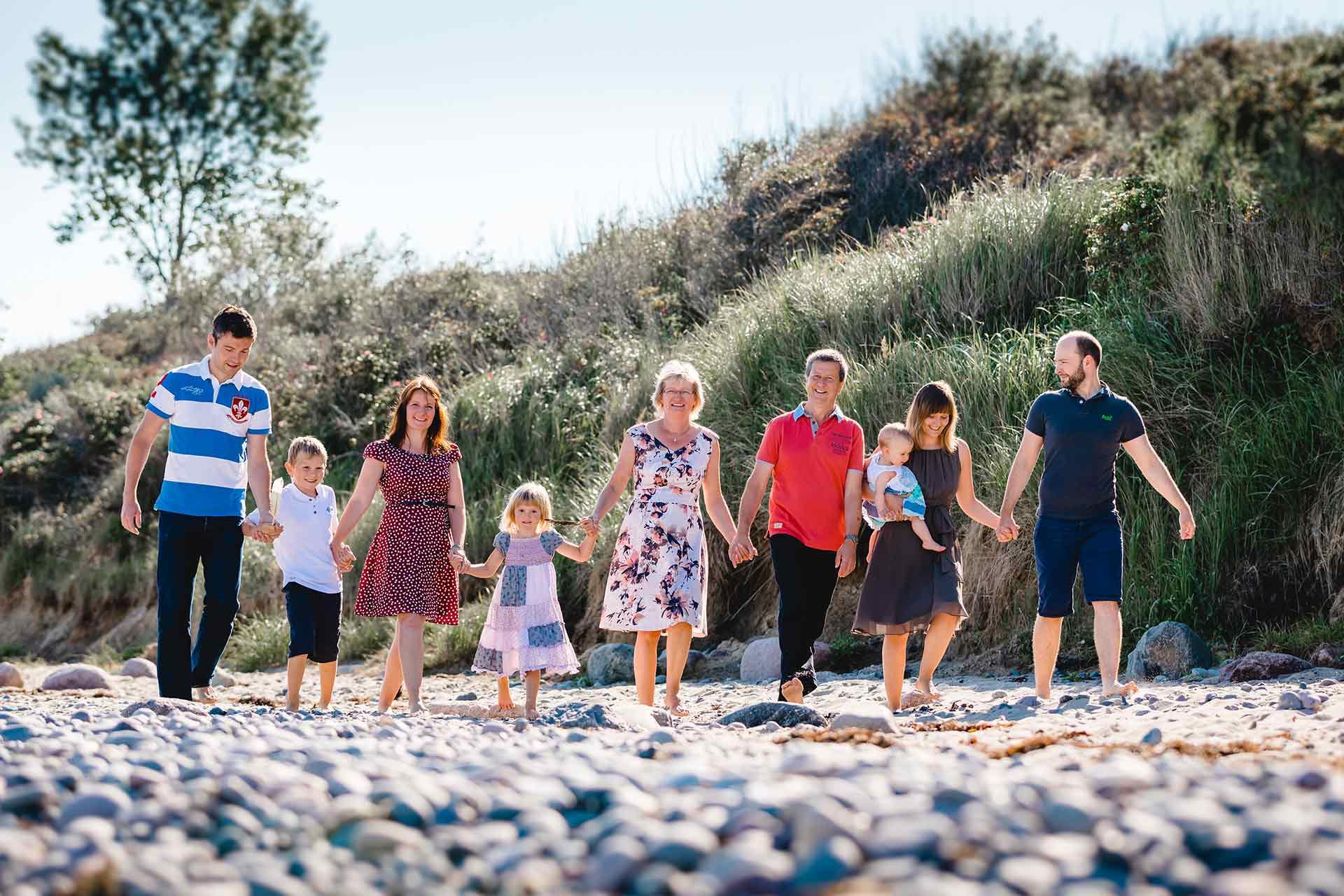 drei-Generationen-neun-Menschen-gehen-Hand-in-Hand-am-Strand-Shooting-am-Strand-Familienfotografie-Fotograf-Rostock - Familienshooting