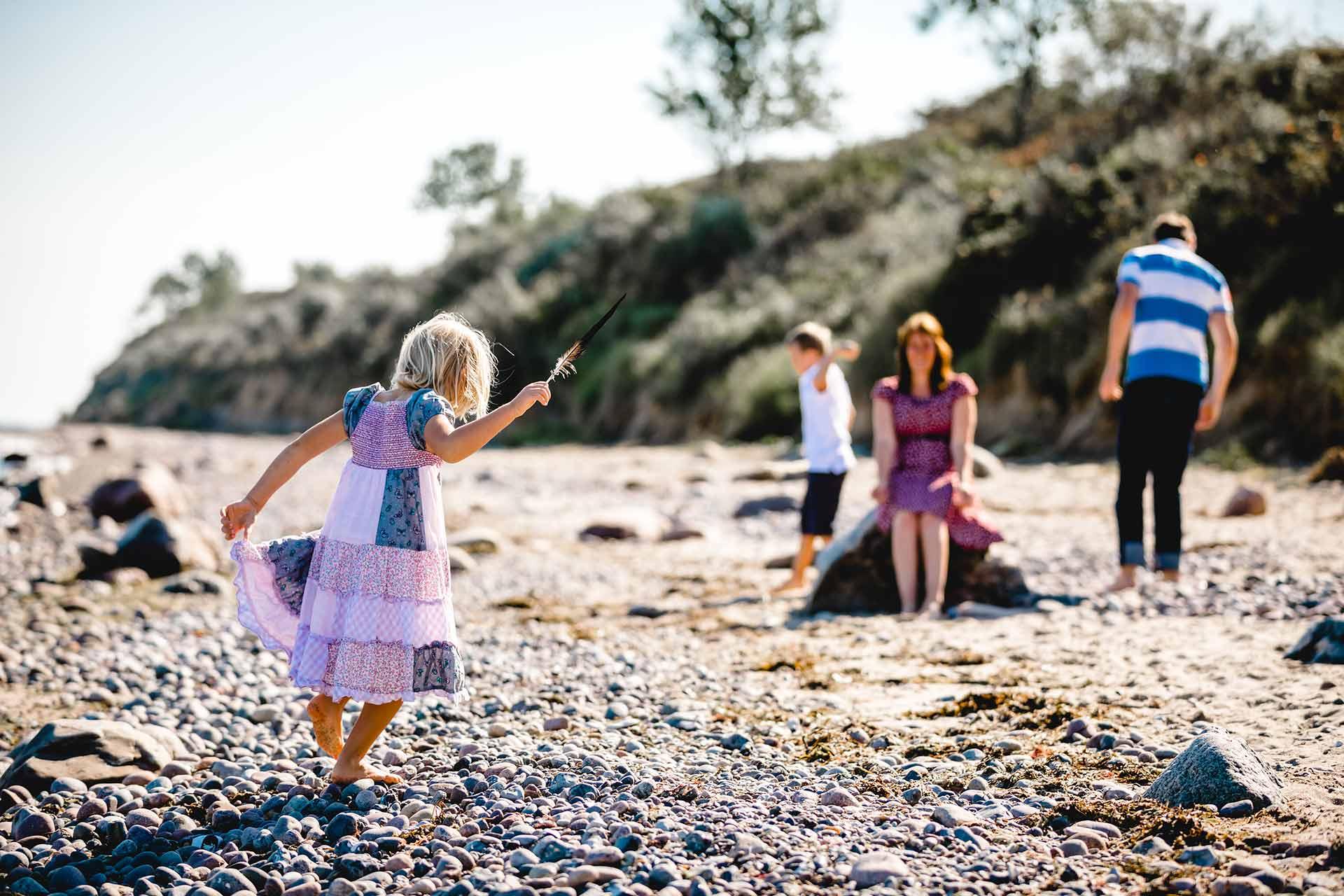 Kind-mit-Vogelfeder-in-der-Hand-Shooting-am-Strand-Familienfotografie-Fotograf-Rostock - Familienshooting