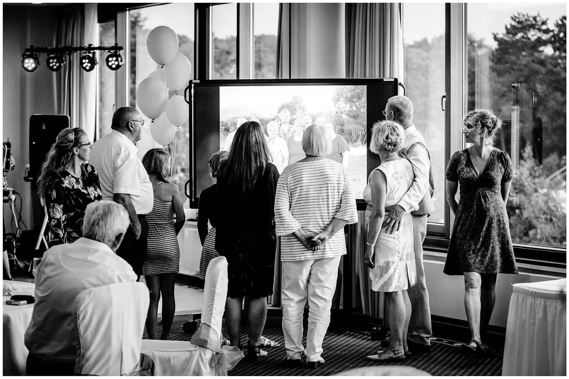 Gaeste-schauen-sich-Diashow-auf-fernseher-an-Hochzeit-im-Hotel-Neptun-Hochzeitsfotograf-Warnemuende-Hochzeitsfotograf-Rostock-Hochzeitsfotograf-Ostseebad-Warnemuende