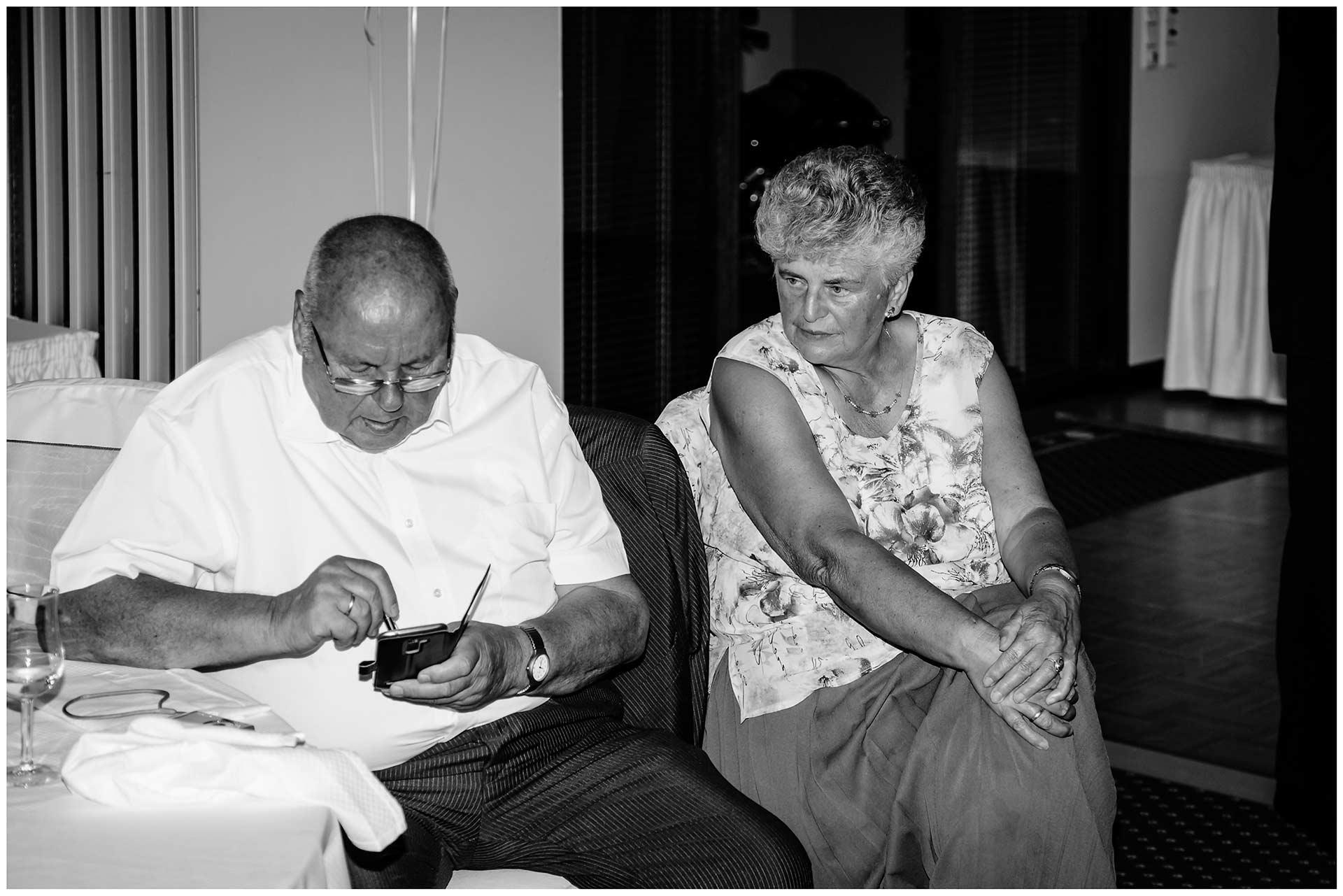 Hochzeitsgast-schaut-auf-sein-Handy-und-wird-von-seiner-Frau-dabei-beobachtet-Hochzeit-im-Hotel-Neptun-Hochzeitsfotograf-Warnemuende-Hochzeitsfotograf-Rostock-Hochzeitsfotograf-Ostseebad-Warnemuende