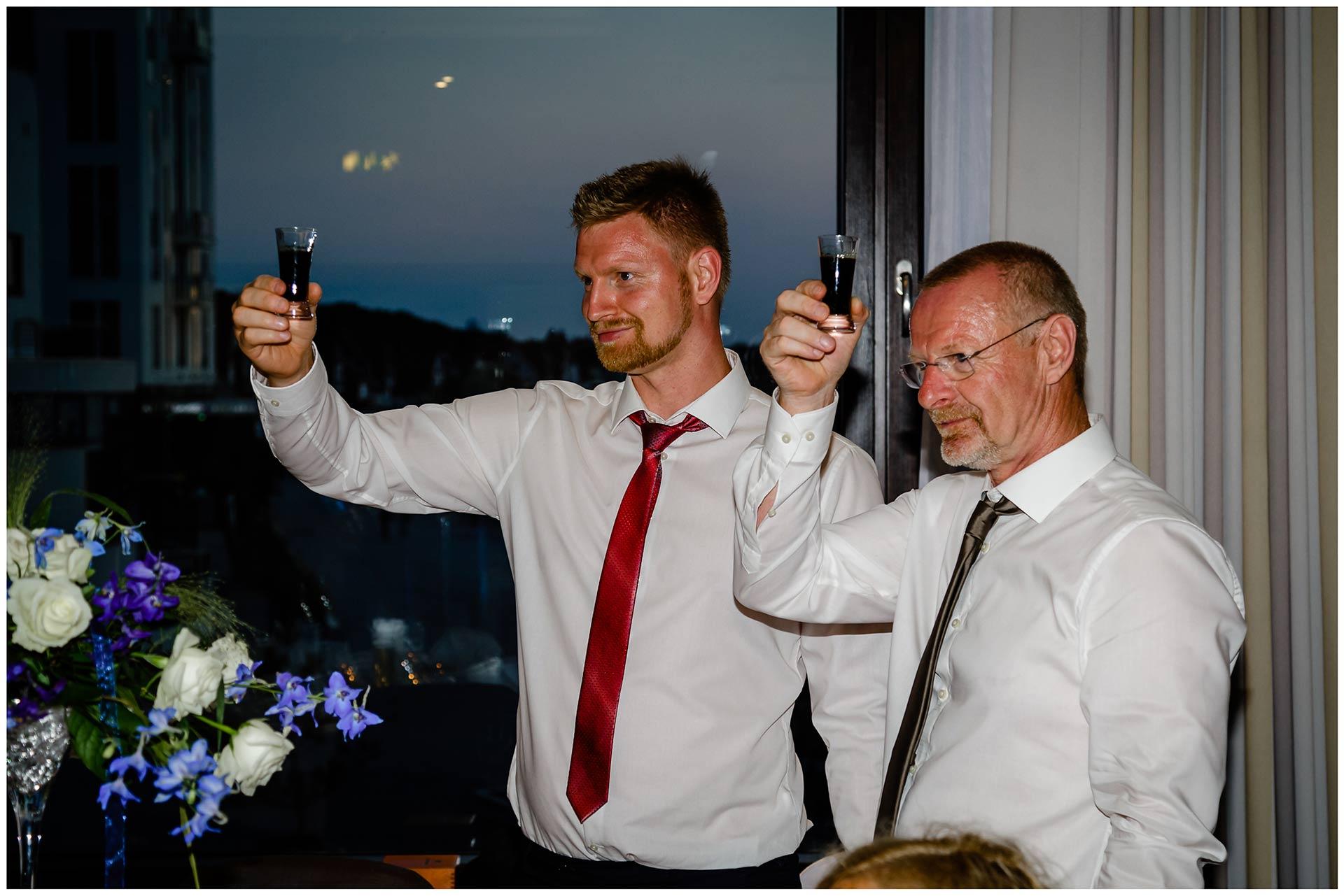 zwei-Maenner-erheben-ihr-Glas-Hochzeit-im-Hotel-Neptun-Hochzeitsfotograf-Warnemuende-Hochzeitsfotograf-Rostock-Hochzeitsfotograf-Ostseebad-Warnemuende