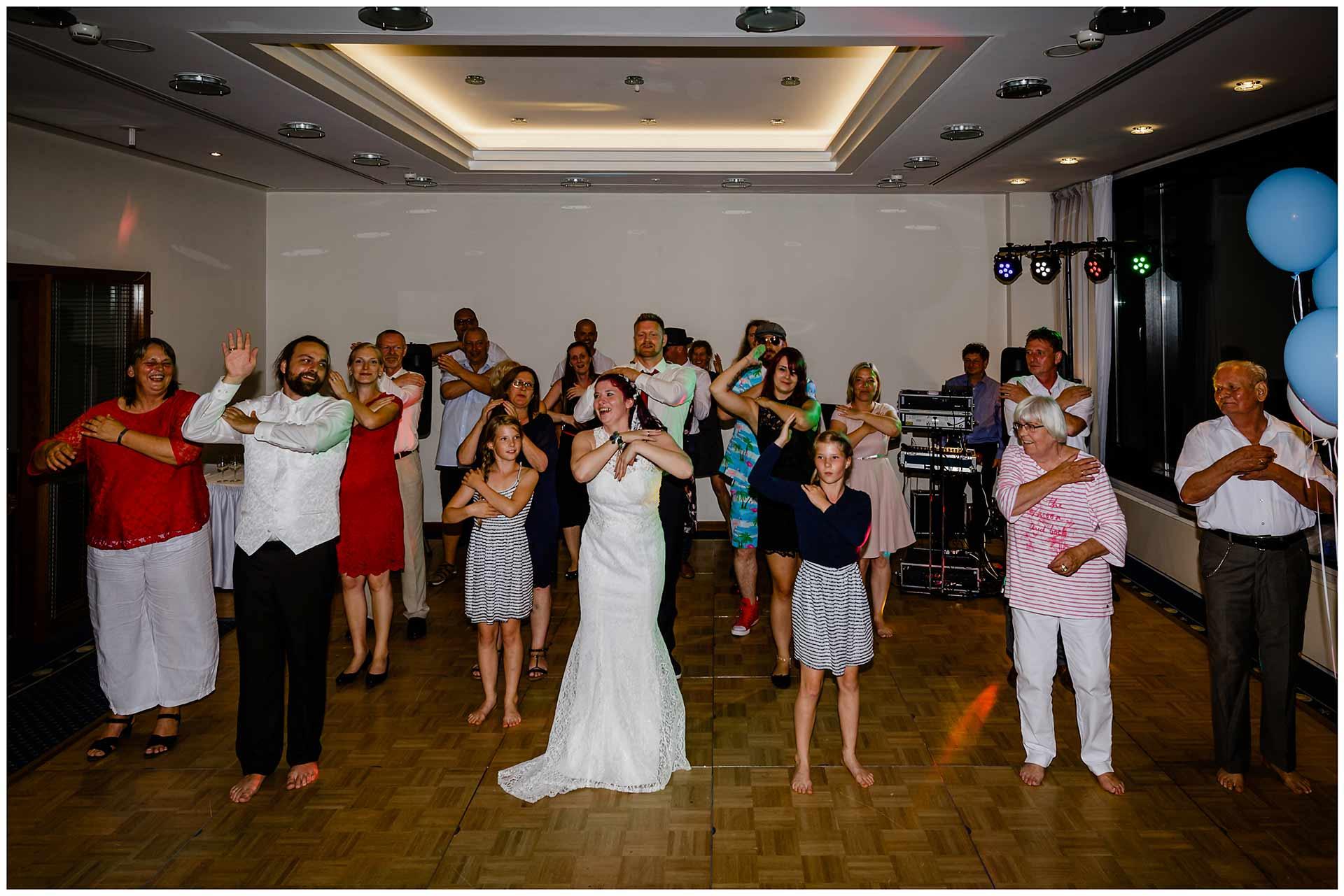 Hochzeitspaar-und-Gaeste-tanzen-Hochzeit-im-Hotel-Neptun-Hochzeitsfotograf-Warnemuende-Hochzeitsfotograf-Rostock-Hochzeitsfotograf-Ostseebad-Warnemuende
