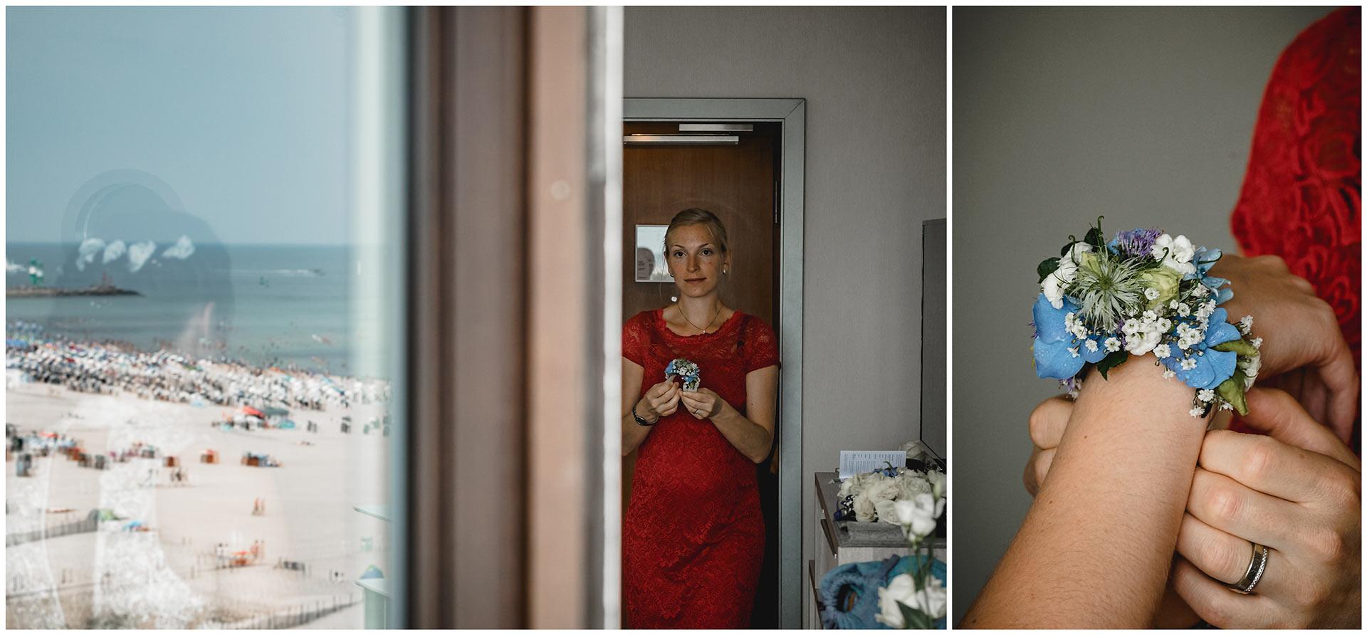 Trauzeugin-bringt-den-Blumenschmuck-und-legt-ihn-ans-Handgelenk-der-Braut-Hochzeitsfotograf-Warnemuende-Rostock-Hochzeitsfotograf-Ostseebad-Warnemuende