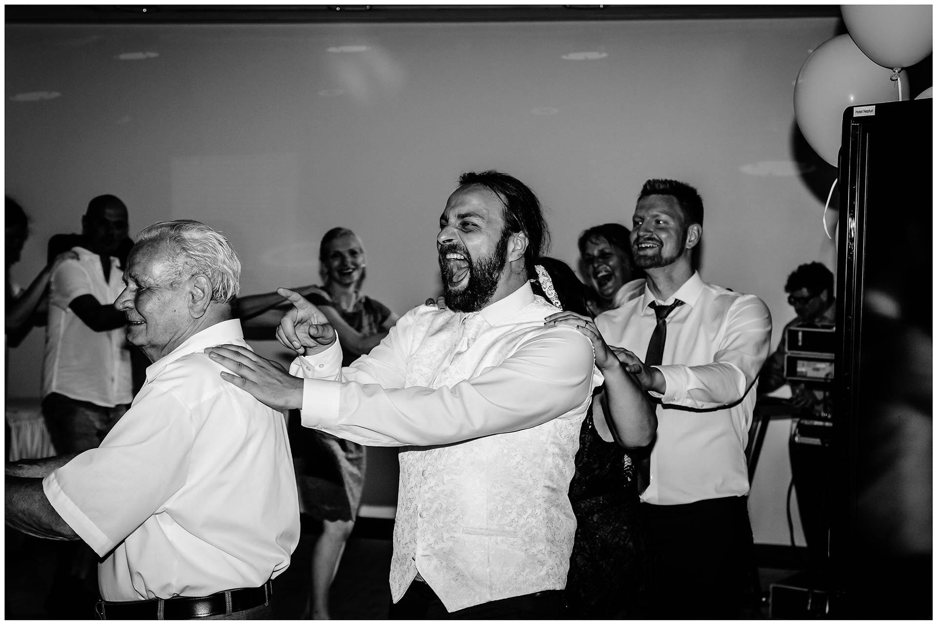 Braeutigam-und-Gaeste-tanzen-eine-Polonaise-Hochzeit-im-Hotel-Neptun-Hochzeitsfotograf-Warnemuende-Hochzeitsfotograf-Rostock-Hochzeitsfotograf-Ostseebad-Warnemuende