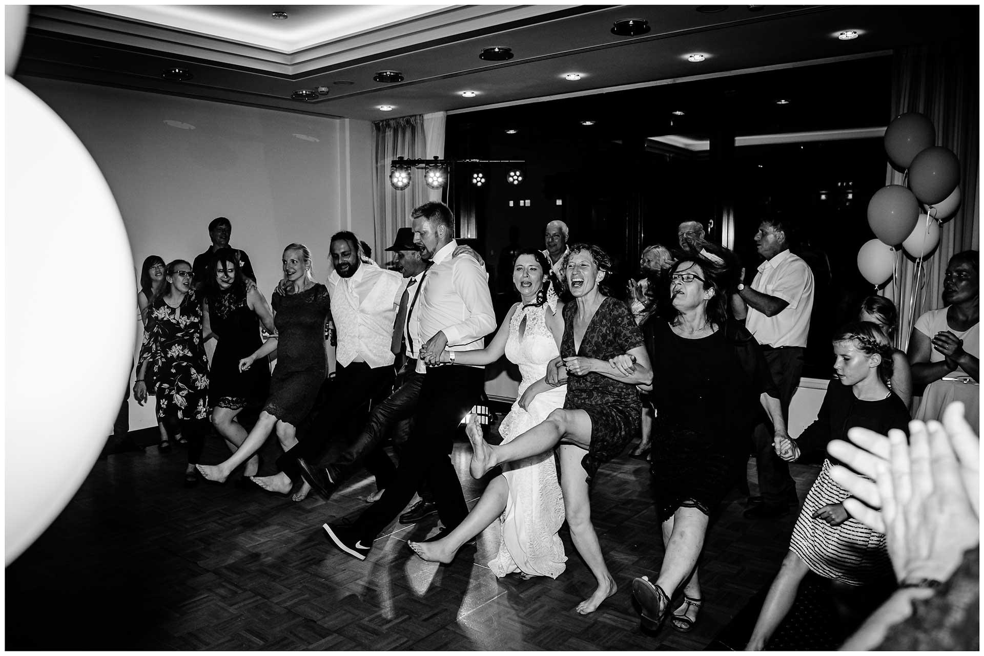 Brautpaar-und-Gaeste-tanzen-ausgelassen-Hochzeit-im-Hotel-Neptun-Hochzeitsfotograf-Warnemuende-Hochzeitsfotograf-Rostock-Hochzeitsfotograf-Ostseebad-Warnemuende