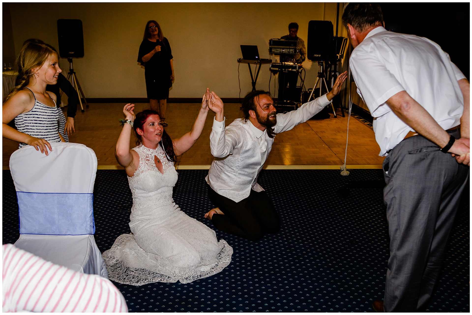 Brautpaar-kniet-auf-dem-Boden-und-beten-aus-Spass-den-Brautvater-an-Hochzeit-im-Hotel-Neptun-Hochzeitsfotograf-Warnemuende-Hochzeitsfotograf-Rostock-Hochzeitsfotograf-Ostseebad-Warnemuende