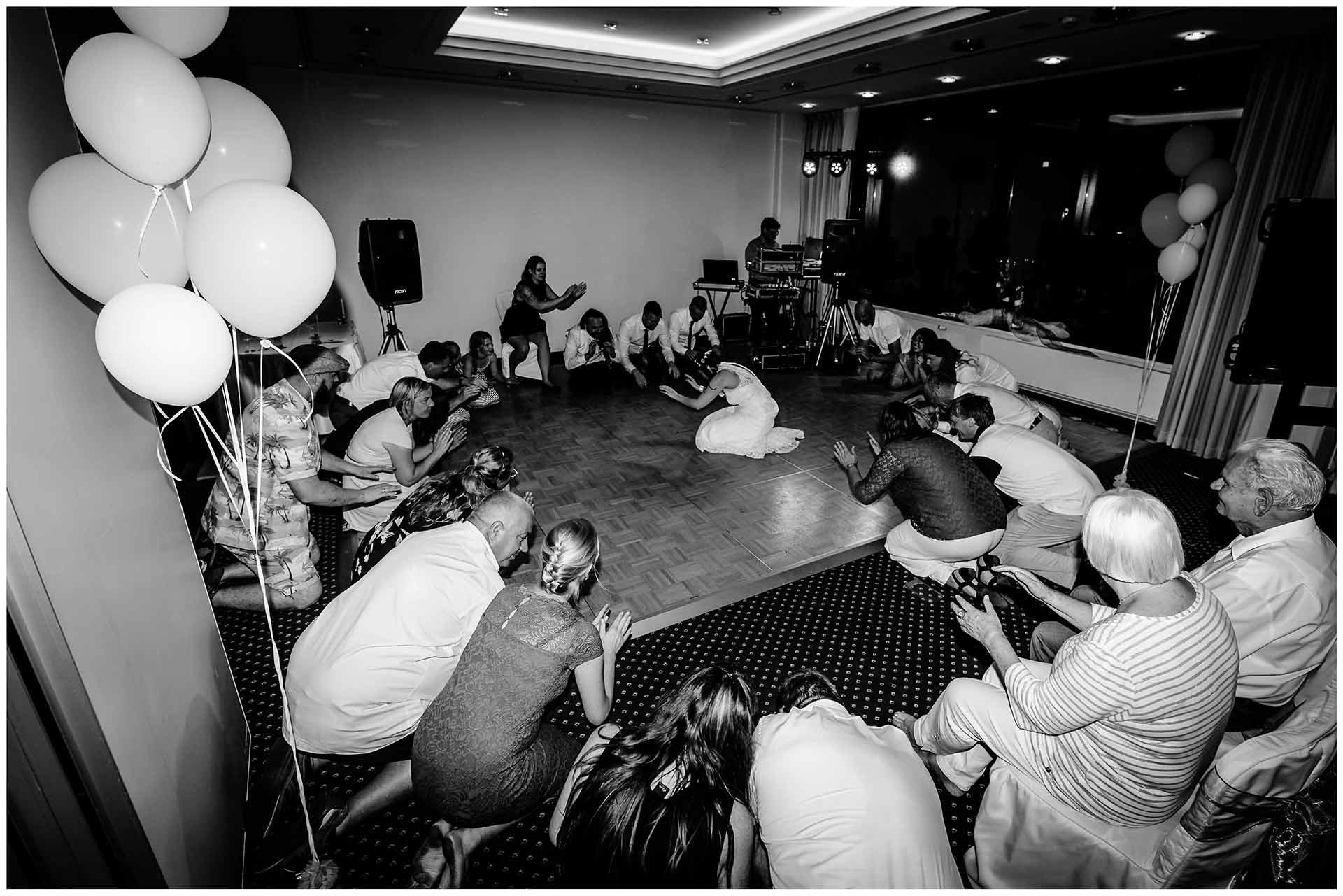 Brautpaar-und-Gaeste-knieen-auf-dem-Boden-We-will-rock-you-Queen-Hochzeit-im-Hotel-Neptun-Hochzeitsfotograf-Warnemuende-Hochzeitsfotograf-Rostock-Hochzeitsfotograf-Ostseebad-Warnemuende