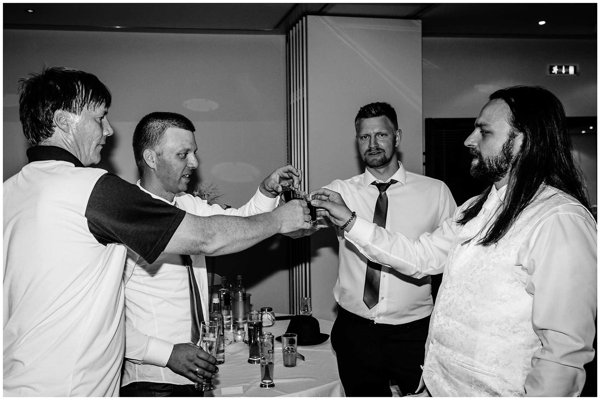Braeutigam-stoesst-mit-Gaesten-an-Hochzeit-im-Hotel-Neptun-Hochzeitsfotograf-Warnemuende-Hochzeitsfotograf-Rostock-Hochzeitsfotograf-Ostseebad-Warnemuende