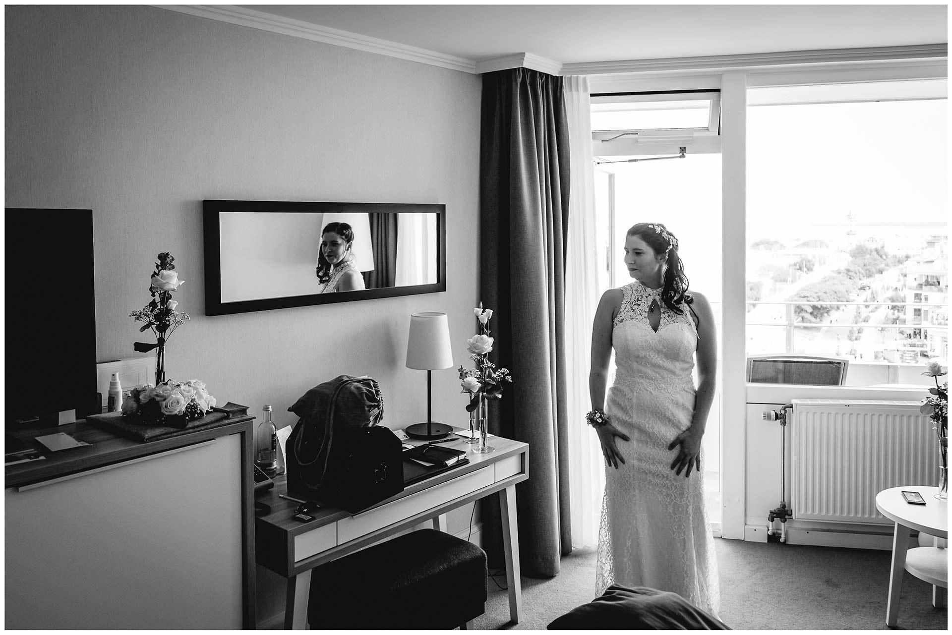 Braut-im-Brautkleid-steht-im-Hotelzimmer-Hochzeitsfotograf-Warnemuende-Rostock-Hochzeitsfotograf-Ostseebad-Warnemuende