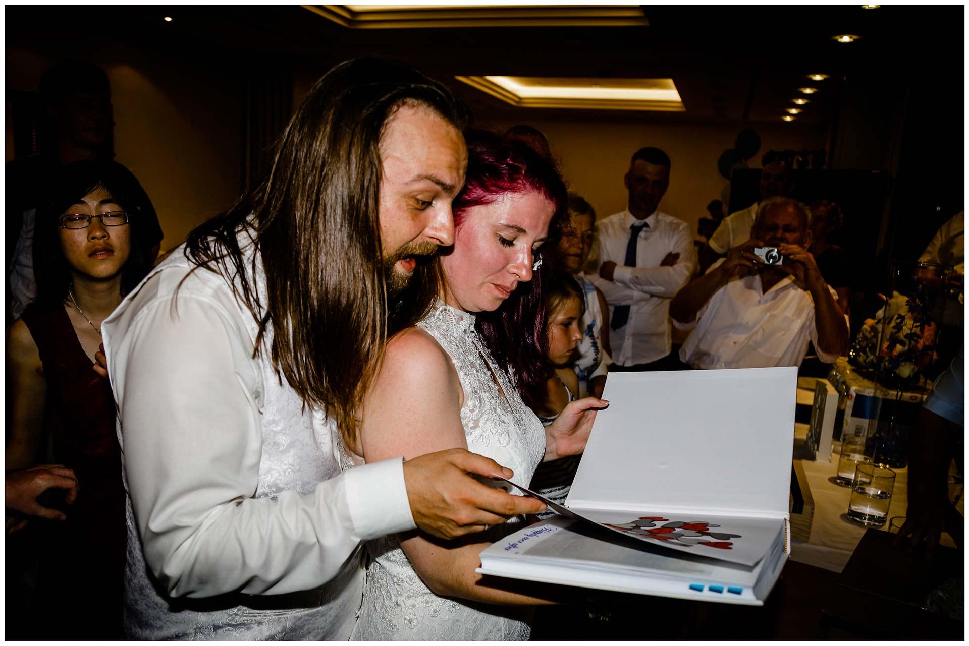 Hochzeitspaar-schaut-sich-ein-Fotoalbum-an-Hochzeit-im-Hotel-Neptun-Hochzeitsfotograf-Warnemuende-Hochzeitsfotograf-Rostock-Hochzeitsfotograf-Ostseebad-Warnemuende