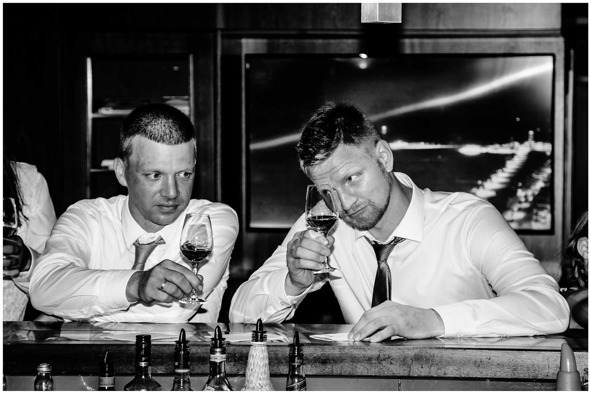 zwei-Hochzeitsgaeste-schauen-auf-ihr-Whiskey-Glas-Hochzeit-im-Hotel-Neptun-Hochzeitsfotograf-Warnemuende-Hochzeitsfotograf-Rostock-Hochzeitsfotograf-Ostseebad-Warnemuende