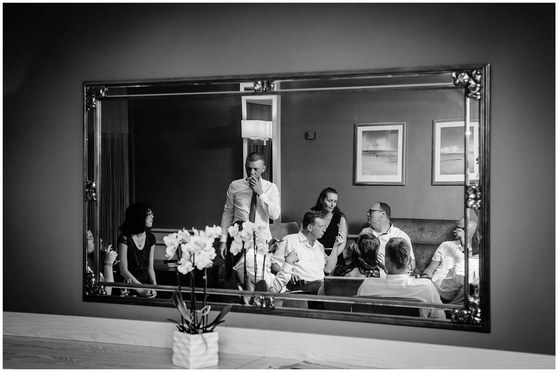 Gäste-der-Hochzeit-sind-in-einem-Spiegel-zu-sehen-und-rauchen-Zigarre-Hochzeit-im-Hotel-Neptun-Hochzeitsfotograf-Warnemuende-Hochzeitsfotograf-Rostock-Hochzeitsfotograf-Ostseebad-Warnemuende