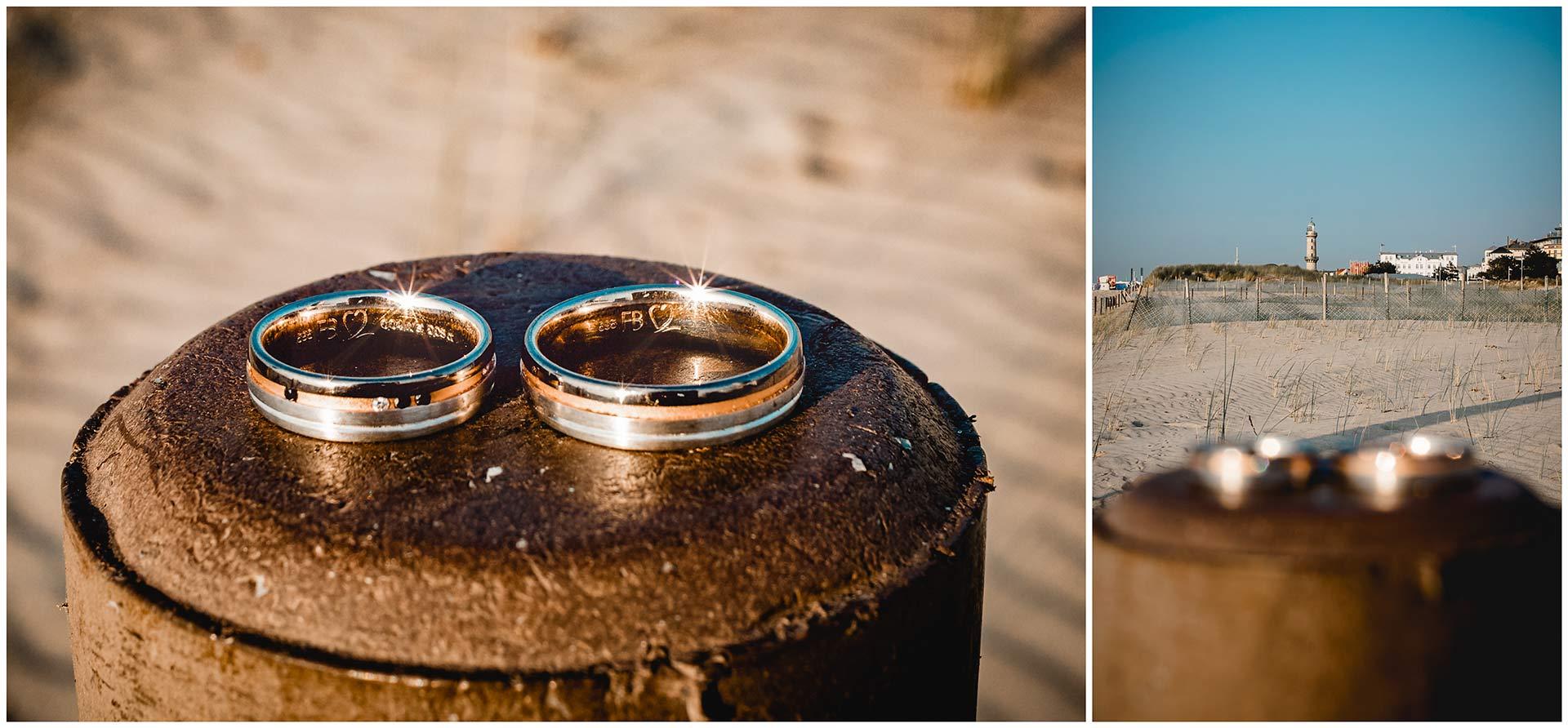 Eheringe-liegen-nebeneinander-im-Hintergrund-der-Leuchtturm-von-Warnemuende-Hochzeit-am-Strand-Hochzeitsfotograf-Warnemuende-Hochzeitsfotograf-Rostock-Hochzeitsfotograf-Ostseebad-Warnemuende