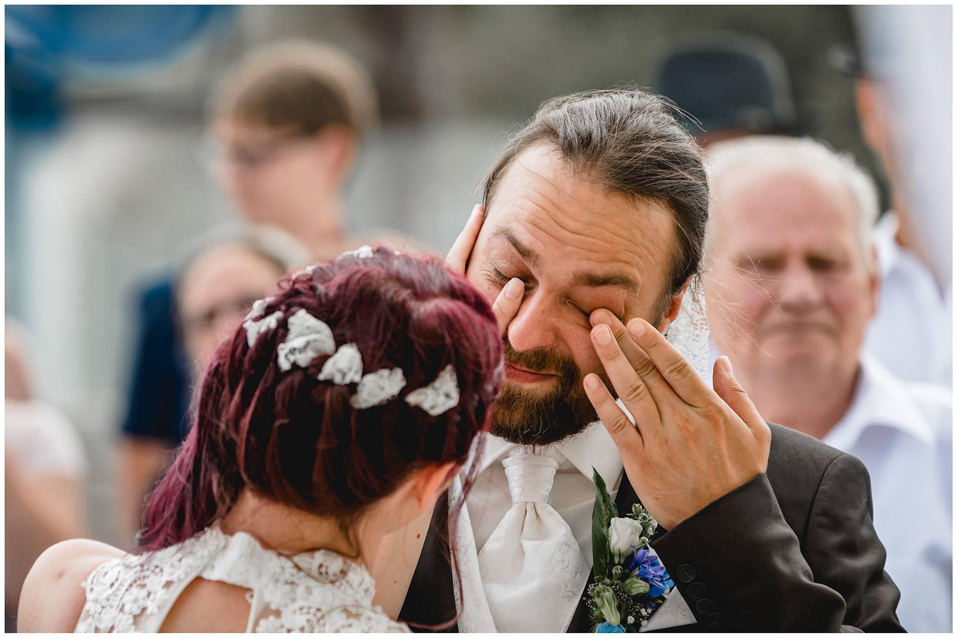 Braut-streicht-liebevoll-eine-Traene-von-der-Wange-ihres-Mannes-Hochzeit-am-Strand-Hochzeitsfotograf-Warnemuende-Hochzeitsfotograf-Rostock-Hochzeitsfotograf-Ostseebad-Warnemuende