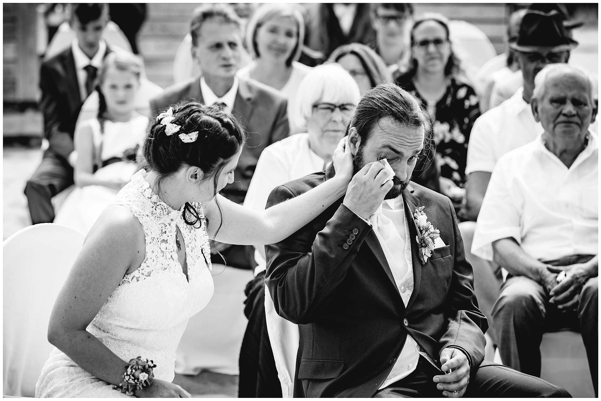 Braut-streichelt-liebevoll-die-Wange-ihres-Mannes_Braeutigam-wischt-sich-eine-Traene-aus-seinem-Gesicht-Hochzeit-am-Strand-Hochzeitsfotograf-Warnemuende-Hochzeitsfotograf-Rostock-Hochzeitsfotograf-Ostseebad-Warnemuende