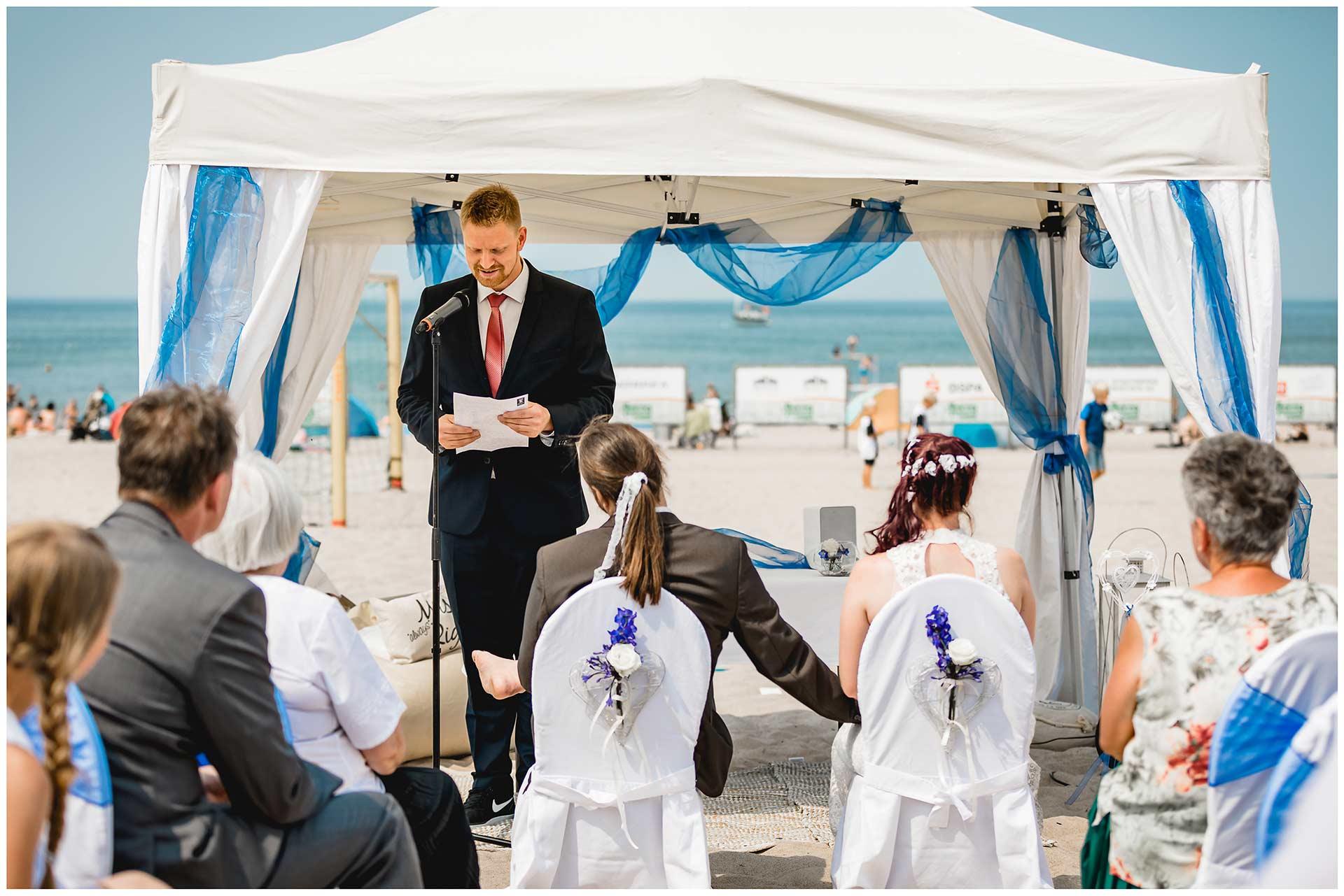 Trauzeuge-haelt-eine-Rede-bei-der-Freien-Trauung-am-Strand-Hochzeit-am-Strand-Hochzeitsfotograf-Warnemuende-Hochzeitsfotograf-Rostock-Hochzeitsfotograf-Ostseebad-Warnemuende