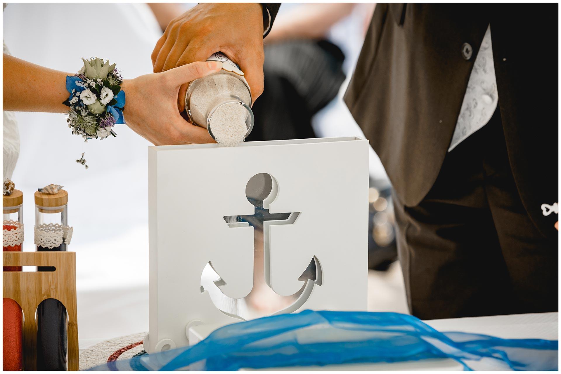 Brautpaar-schuettet-Sand-in-ein-Gefaess_Sandzeremonie-Hochzeit-am-Strand-Hochzeitsfotograf-Warnemuende-Hochzeitsfotograf-Rostock-Hochzeitsfotograf-Ostseebad-Warnemuende