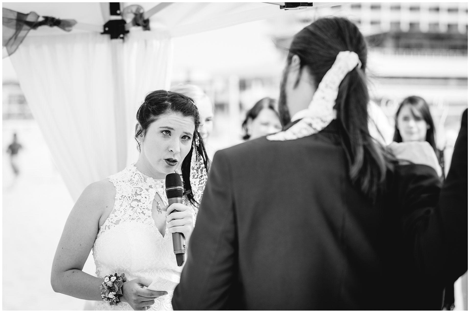 Braut-liest-ihrem-Mann-das-Eheversprechen-vor-Hochzeit-am-Strand-Hochzeitsfotograf-Warnemuende-Hochzeitsfotograf-Rostock-Hochzeitsfotograf-Ostseebad-Warnemuende