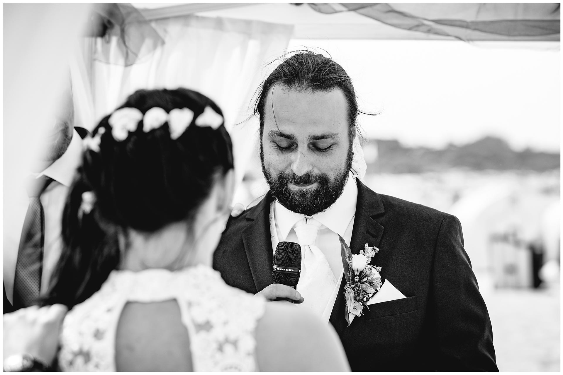 Braeutigam-liest-seiner-Frau-das-Eheversprechen-vor-Hochzeit-am-Strand-Hochzeitsfotograf-Warnemuende-Hochzeitsfotograf-Rostock-Hochzeitsfotograf-Ostseebad-Warnemuende