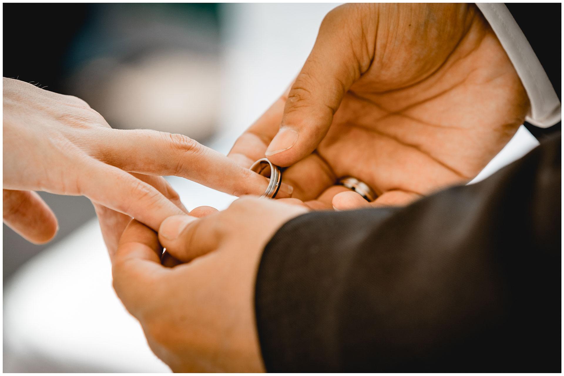 Braeutigam-steckt-seine-Frau-den-Ehering-auf-Hochzeit-am-Strand-Hochzeitsfotograf-Warnemuende-Hochzeitsfotograf-Rostock-Hochzeitsfotograf-Ostseebad-Warnemuende
