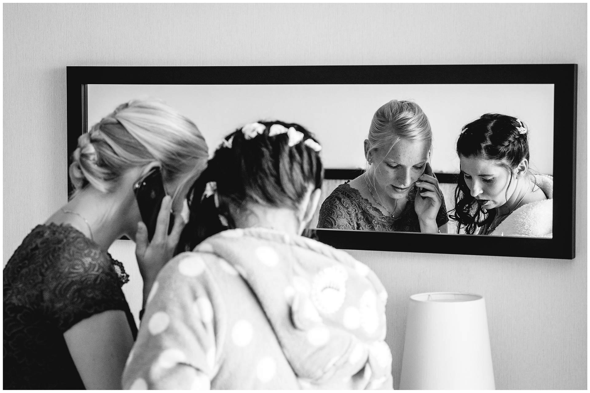 Spiegelbild-von-Braut-und-Trauzeugin-sie-telefonieren-Hochzeitsfotograf-Warnemuende-Rostock-Hochzeitsfotograf-Ostseebad-Warnemuende
