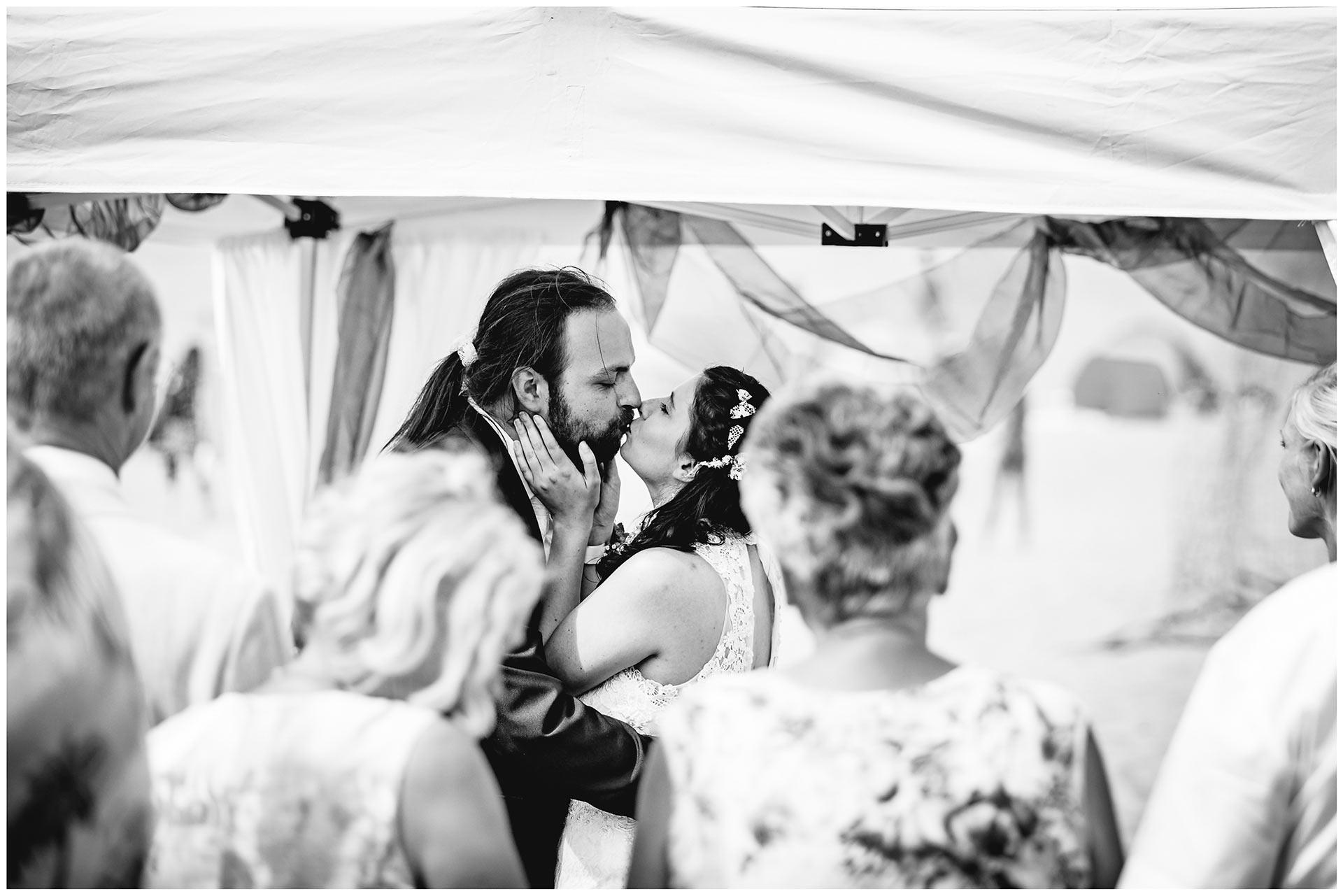 Hochzeitspaar-kuesst-sich-liebevoll-Hochzeit-am-Strand-Hochzeitsfotograf-Warnemuende-Hochzeitsfotograf-Rostock-Hochzeitsfotograf-Ostseebad-Warnemuende