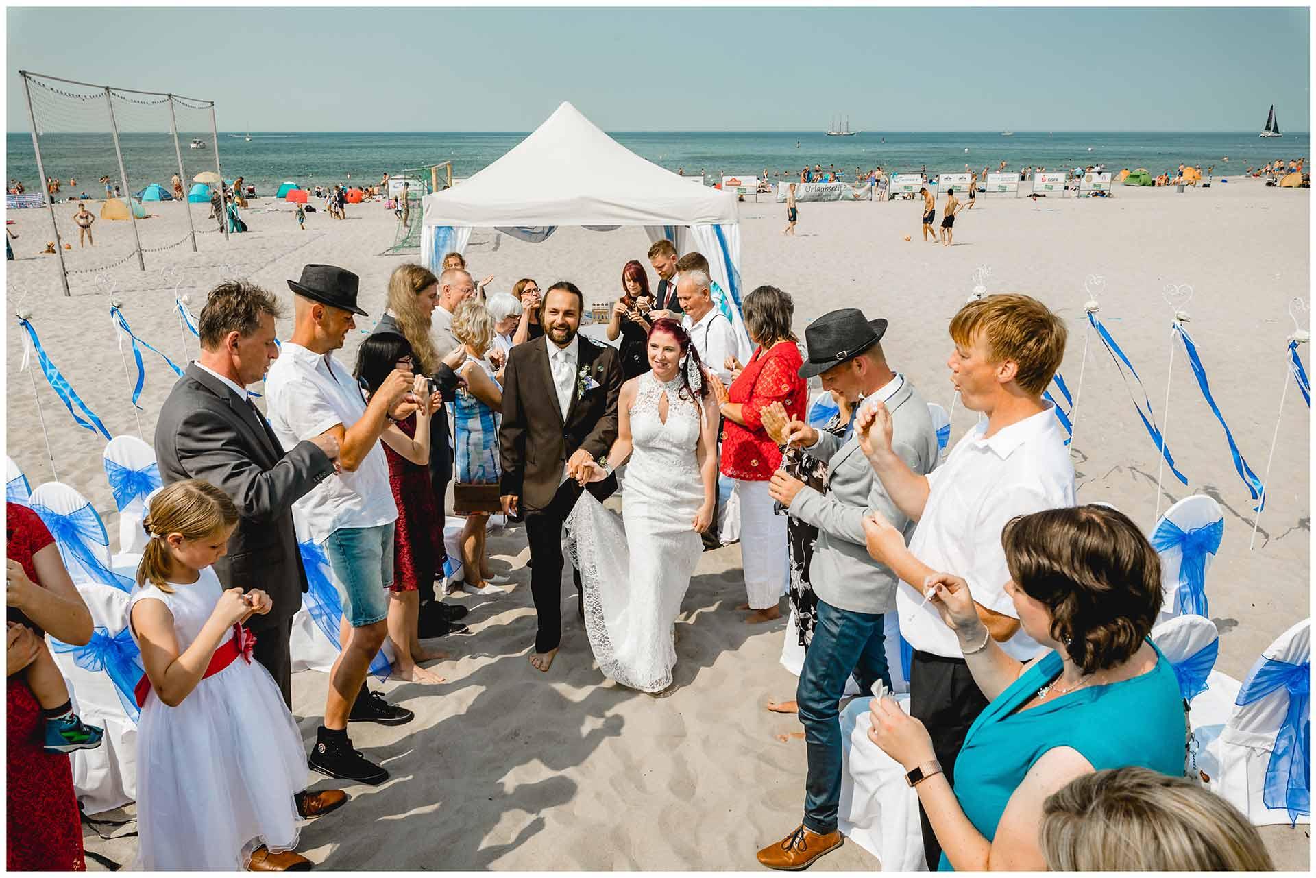 Brautpaar-nach-der-Freien-Trauung-am-Strand_Gaeste-stehen-Spalier-Hochzeit-am-Strand-Hochzeitsfotograf-Warnemuende-Hochzeitsfotograf-Rostock-Hochzeitsfotograf-Ostseebad-Warnemuende
