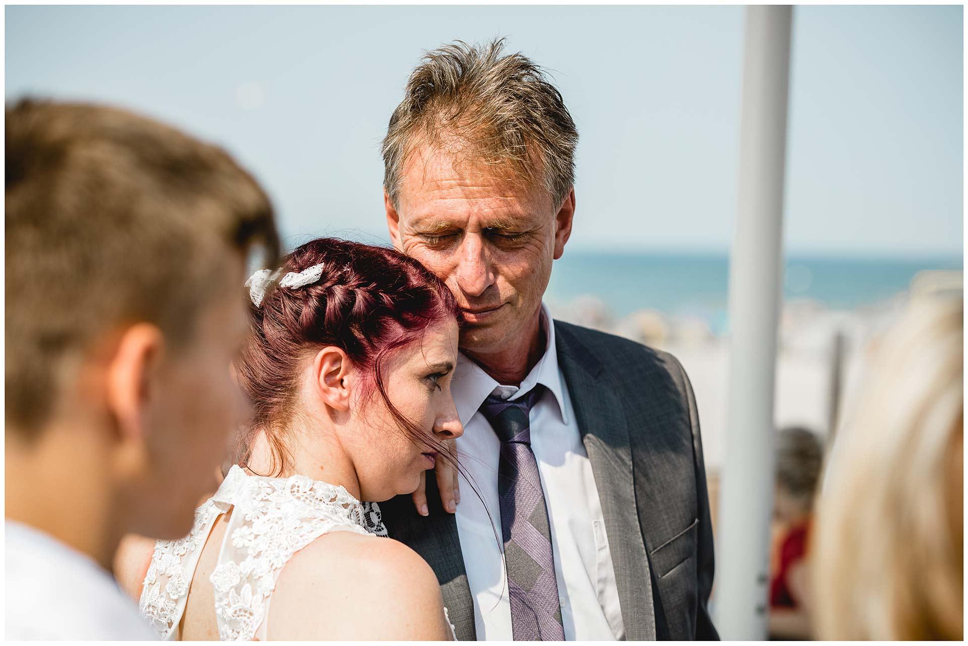Braut-kuschelt-mit-ihrem-Vater-Hochzeitsfotograf-Warnemuende-Hochzeitsfotograf-Rostock-Hochzeitsfotograf-Ostseebad-Warnemuende