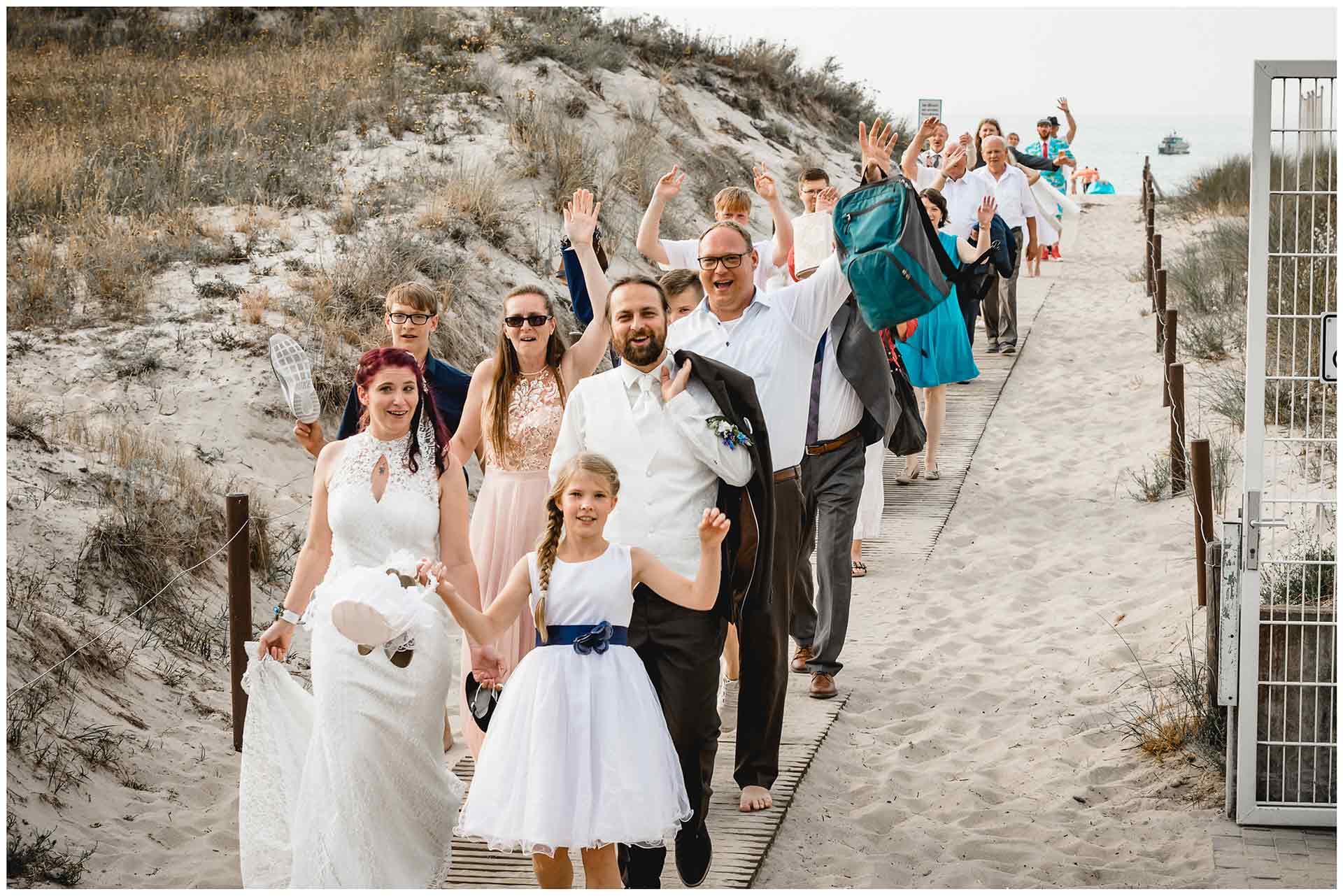 Brautpaar-und-Gaeste-gehen-nach-Freier-Trauung-am-Strand-zurueck-ins-Hotel-Neptun-Hochzeit-am-Strand-Hochzeitsfotograf-Warnemuende-Hochzeitsfotograf-Rostock-Hochzeitsfotograf-Ostseebad-Warnemuende