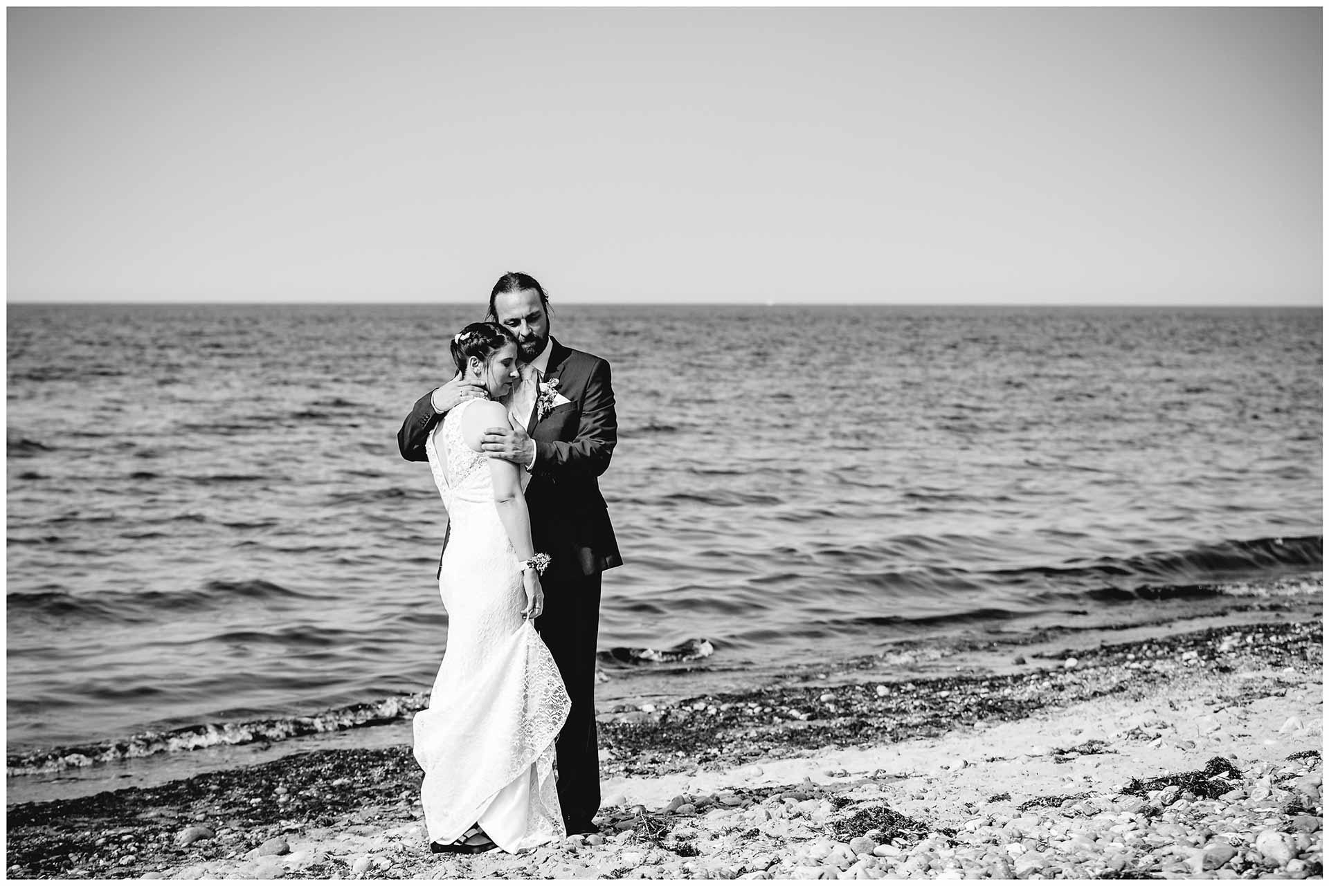 Hochzeitspaar-steht-Arm-in-Arm-mit-geschlossenen-Augen-am-Ostseestrand-Hochzeitsshooting-Hochzeit-am-Strand-Hochzeitsfotograf-Warnemuende-Hochzeitsfotograf-Rostock-Hochzeitsfotograf-Ostseebad-Warnemuende