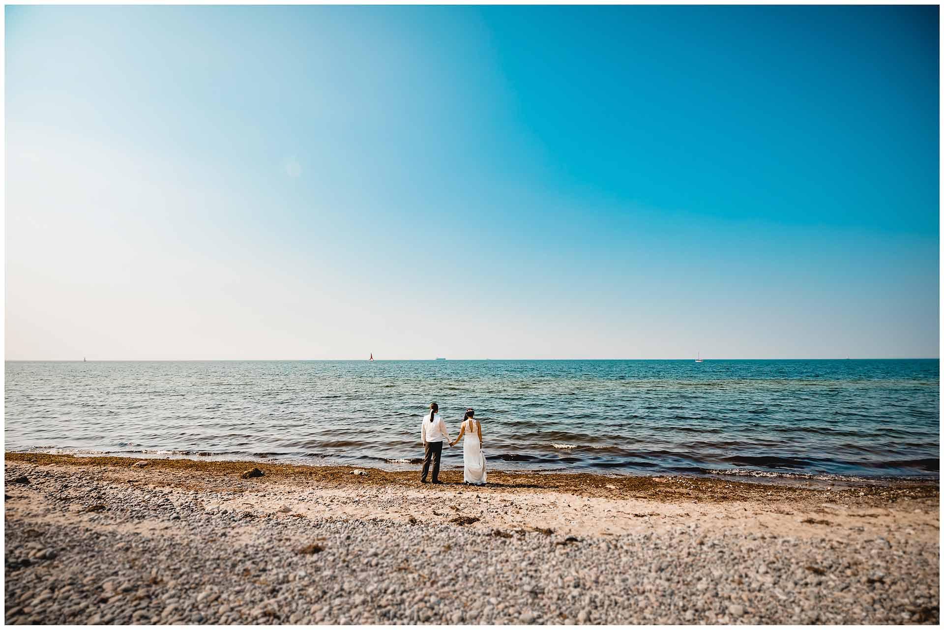 Brautpaar-steht-Hand-in-Hand-direkt-an-der-Ostsee-und-schaut-die-Ferne-Hochzeitsshooting-Hochzeit-am-Strand-Hochzeitsfotograf-Warnemuende-Hochzeitsfotograf-Rostock-Hochzeitsfotograf-Ostseebad-Warnemuende